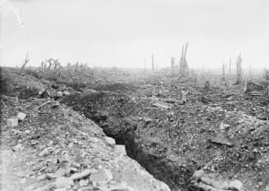 THE BATTLE OF THE SOMME 1 JULY - 18 NOVEMBER 1916: The badly shelled main road to Bapaume through Pozieres, showing a communication trench and broken trees